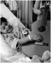 Hospitalized child beams with joy as she helps a musician play a guitar