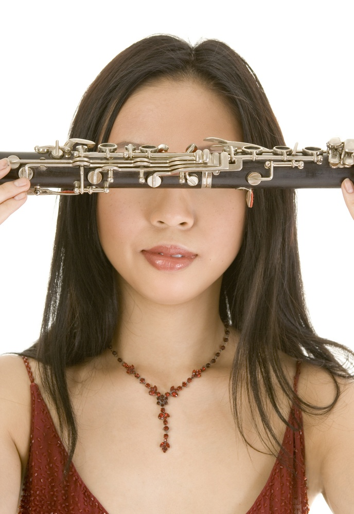 music student holding woodwind instrument over her eyes